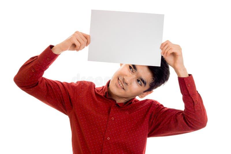 Jeune homme élégant drôle dans la chemise rouge posant avec la plaquette vide dans des ses mains et recherchant d'isolement sur l images libres de droits