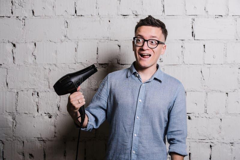 Jeune homme élégant fol avec des expressions hairdraier et drôles sur le mur de briques gris photo stock
