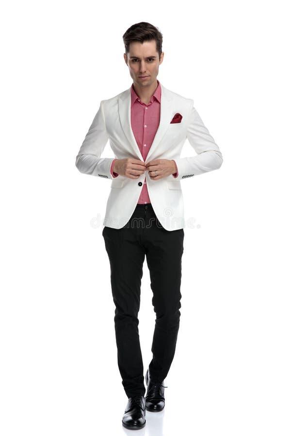 Jeune homme élégant frais marchant et boutonnant son manteau images stock
