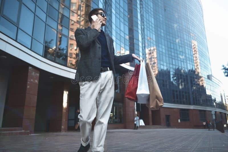 Jeune homme élégant heureux avec le téléphone marchant dans la rue urbaine et appréciant des achats de Black Friday dans les maga images stock