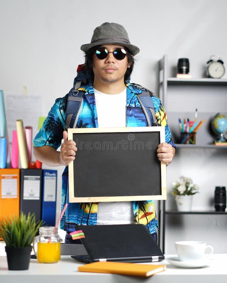 Jeune homme élégant portant le grand sac à dos et tenant le tableau noir a photo stock