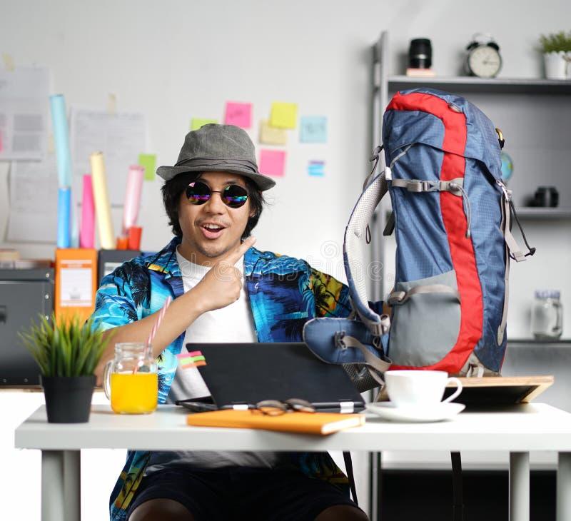 Jeune homme élégant prêt à voyager Pointage du grand sac à dos chez Offi photographie stock