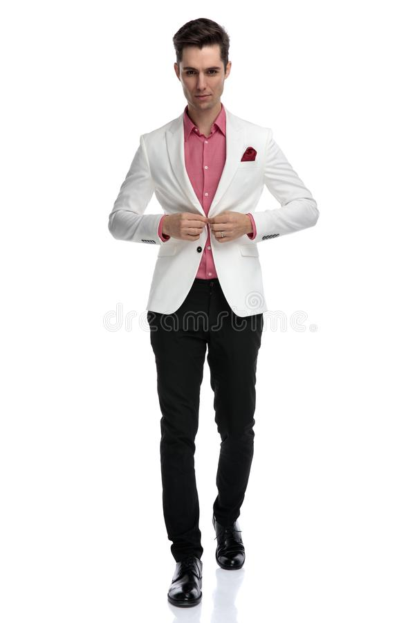 Jeune homme élégant sérieux clôturant son manteau et marche photographie stock