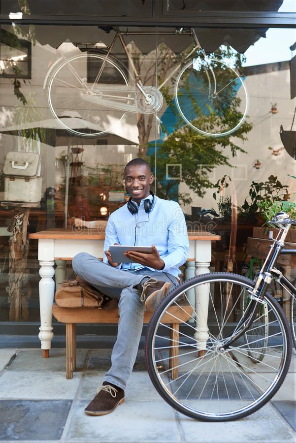 Jeune homme élégant surfant le filet à un café de trottoir photos stock