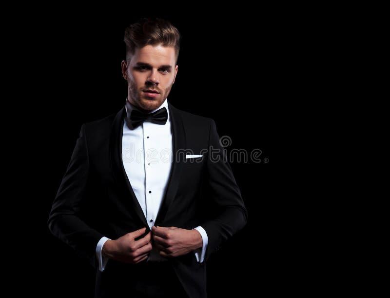 Jeune homme élégant tenant son bouton de manteau photographie stock