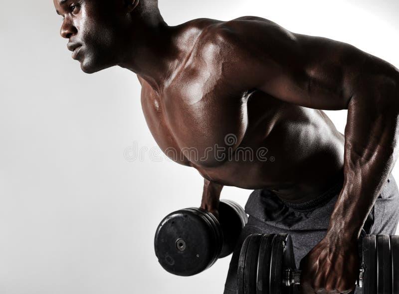 Jeune homme établissant avec les haltères lourdes photos stock