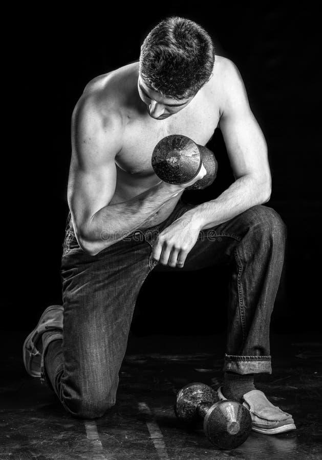 Jeune homme établissant le biceps - boucle de concentration d'haltère image libre de droits