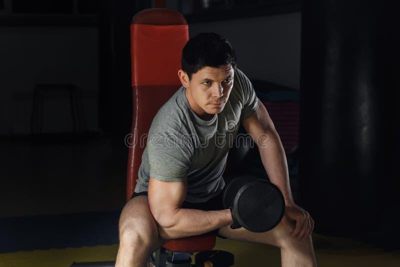 Jeune homme établissant le biceps - boucles de concentration d'haltère images stock