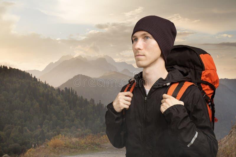 Jeune homme actif trimardant dans la montagne, vue de c?t? sur le fond nuageux de paysage mode de vie et tourisme actifs photographie stock libre de droits