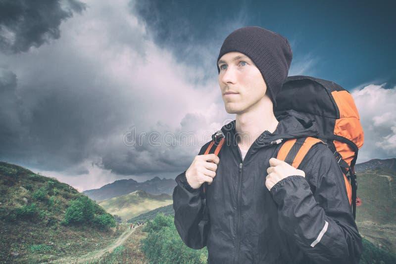 Jeune homme actif trimardant dans la montagne, vue de c?t? sur le fond nuageux de paysage mode de vie et tourisme actifs photo stock