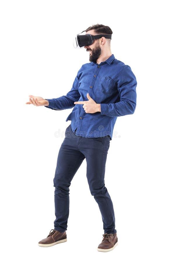 Jeune homme adulte enthousiaste avec des verres de vr simulant le tir avec l'arme automatique jouant le jeu vidéo photo stock