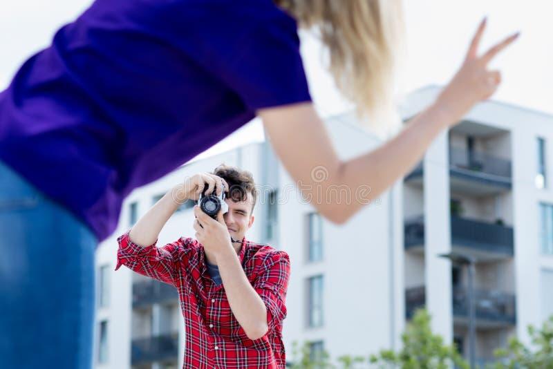 Jeune homme adulte prenant la photo de l'amie image stock