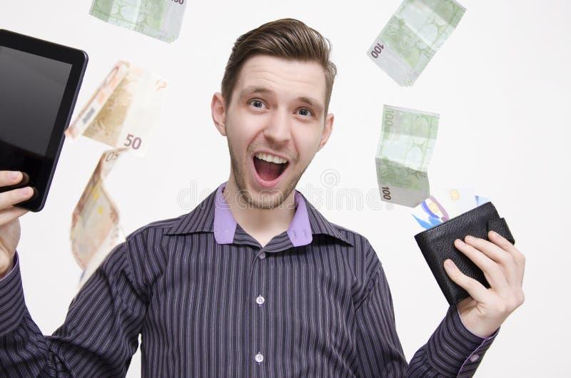 Jeune homme adulte tenant le comprimé et les cartes de crédit, alors que l'argent (euros) tombe de l'air photo libre de droits