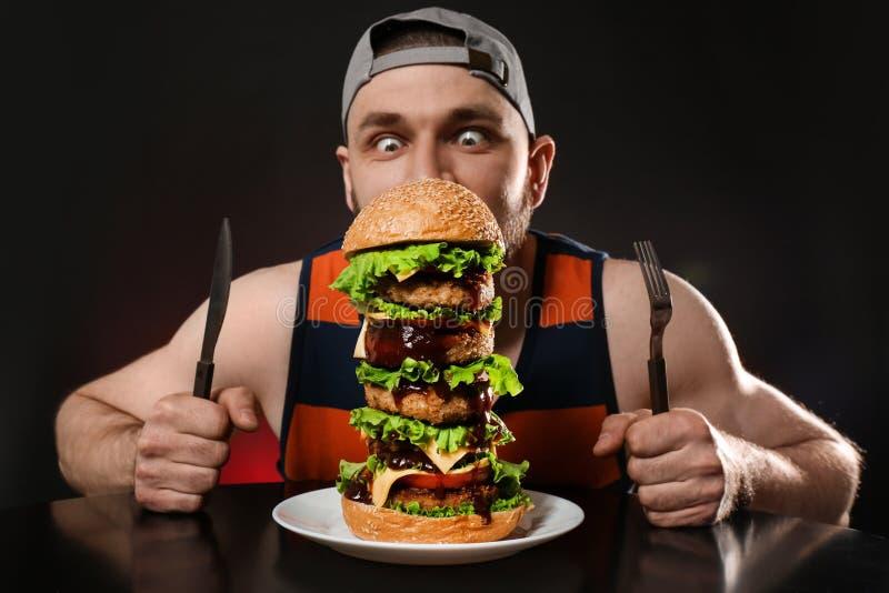 Jeune homme affamé avec des couverts mangeant l'hamburger énorme sur le noir images stock