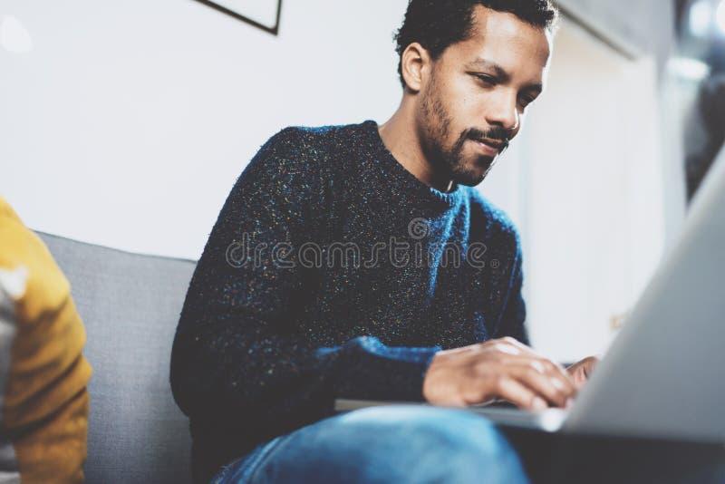 Jeune homme africain à l'aide de l'ordinateur portable tout en se reposant à son endroit coworking moderne Concept des gens d'aff image libre de droits