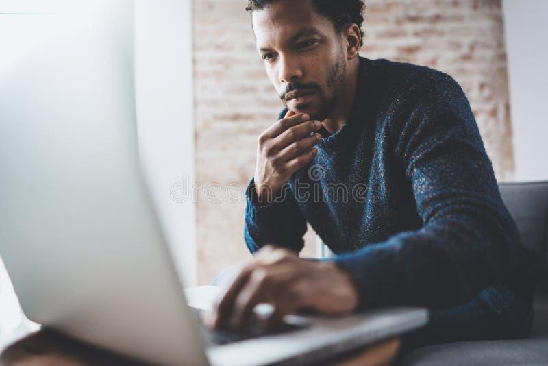 Jeune homme africain à l'aide de l'ordinateur portable tout en se reposant à son endroit coworking moderne Concept des gens d'aff photos libres de droits