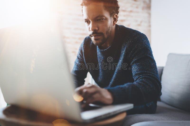 Jeune homme africain attirant à l'aide de l'ordinateur portable tout en se reposant à son endroit coworking moderne Concept des g image libre de droits
