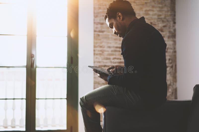 Jeune homme africain barbu à l'aide de l'ordinateur portable tout en se reposant sur le sofa à son siège social moderne Concept d photo libre de droits
