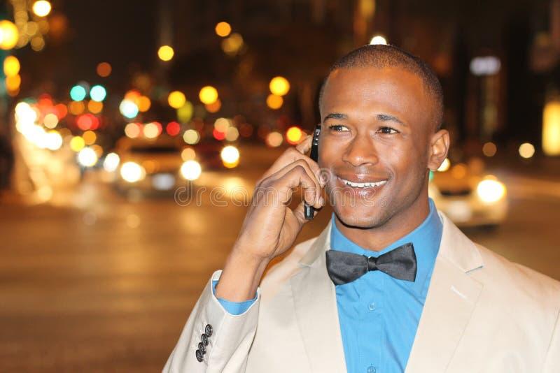 Jeune homme africain beau parlant au téléphone portable dans la ville de nuit avec l'espace de copie photographie stock libre de droits