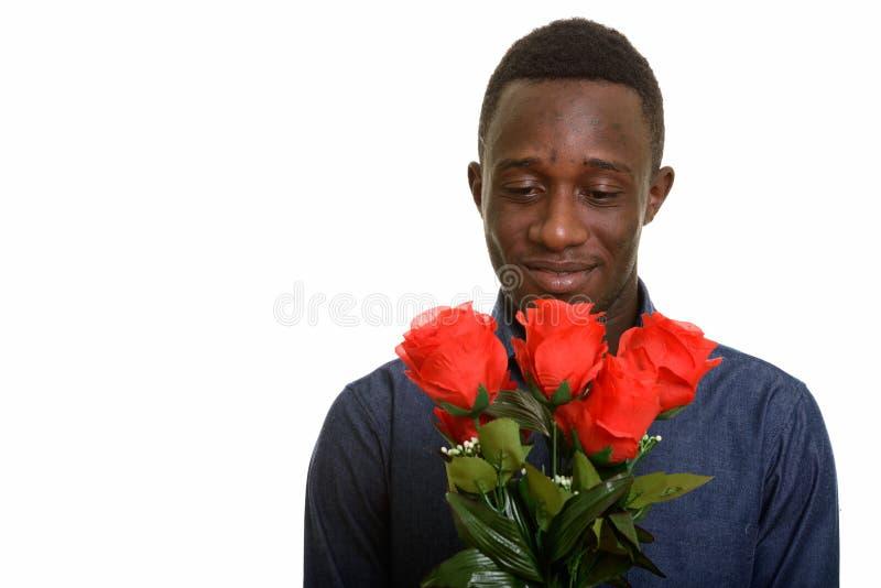 Jeune homme africain bel jugeant les roses rouges prêtes pour Valentine photo stock