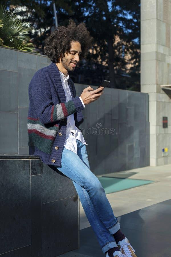 Jeune homme africain bel utilisant son smartphone avec le sourire tout en se reposant sur un extérieur de banc dans le jour ensol images stock