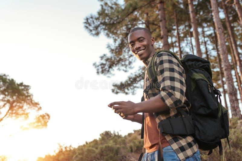 Jeune homme africain de sourire employant des généralistes tout en augmentant image stock