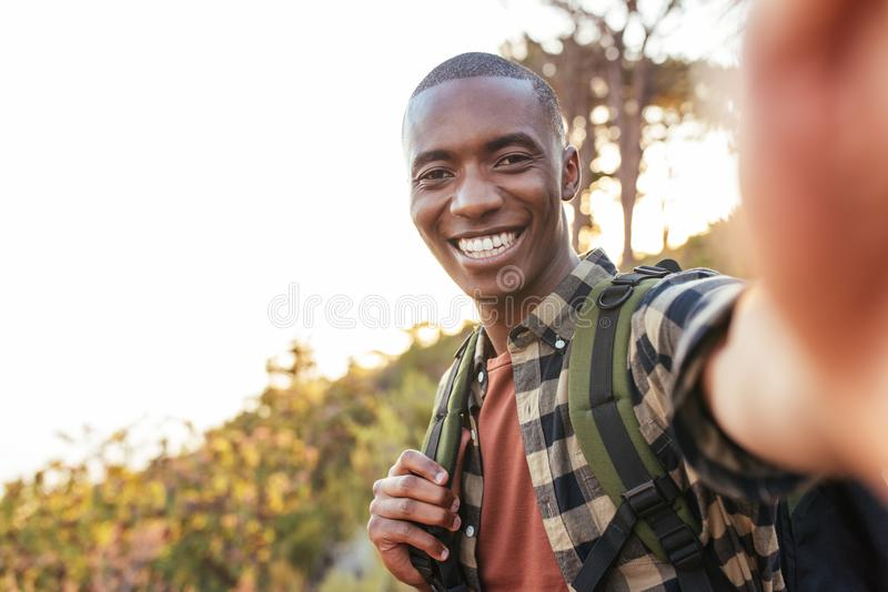 Jeune homme africain de sourire prenant un selfie tout en augmentant dehors image libre de droits