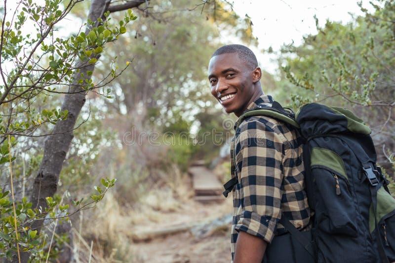 Jeune homme africain de sourire trimardant dans les collines photographie stock libre de droits
