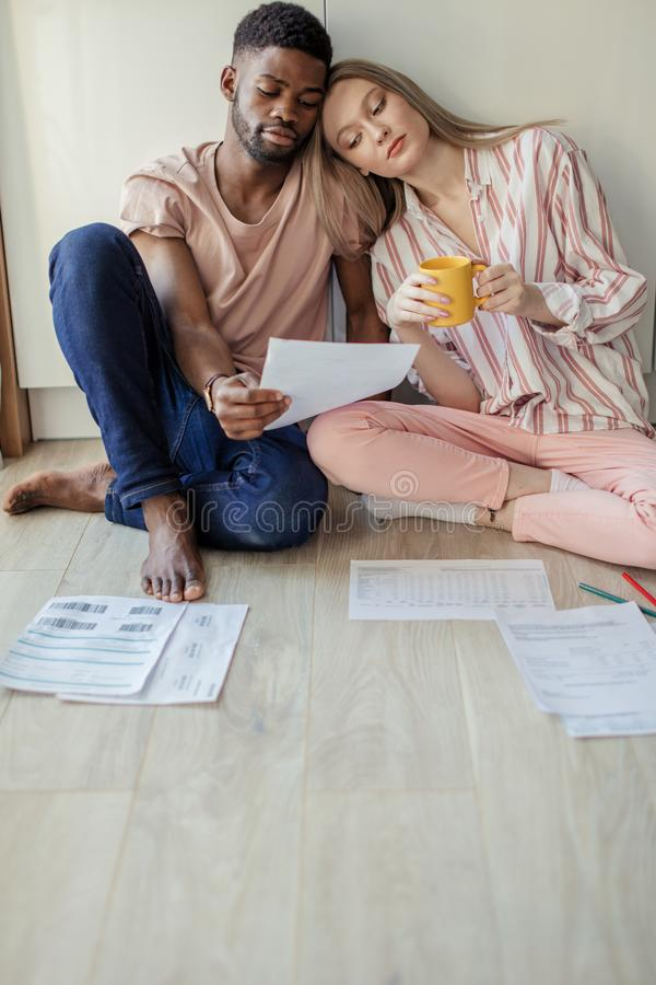 Jeune homme africain et femme européenne avec de longs cheveux regardant des papiers dans la cuisine photo libre de droits