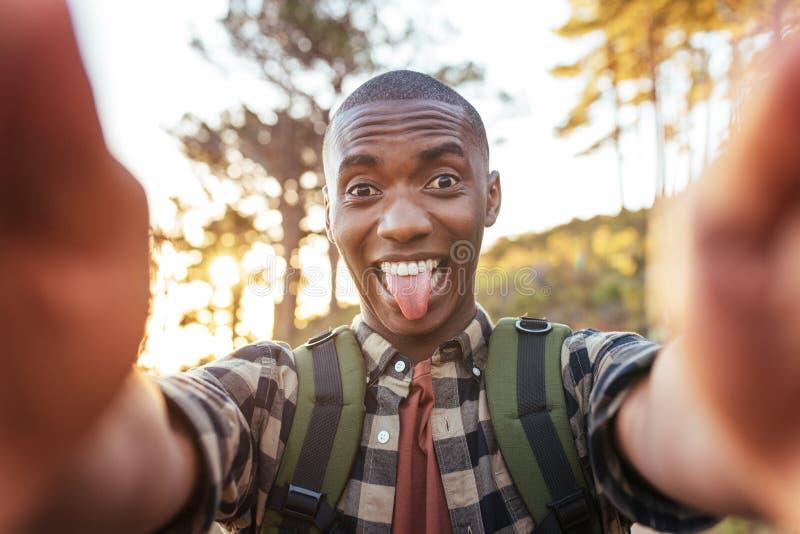 Jeune homme africain faisant des visages et prenant des selfies dehors images libres de droits