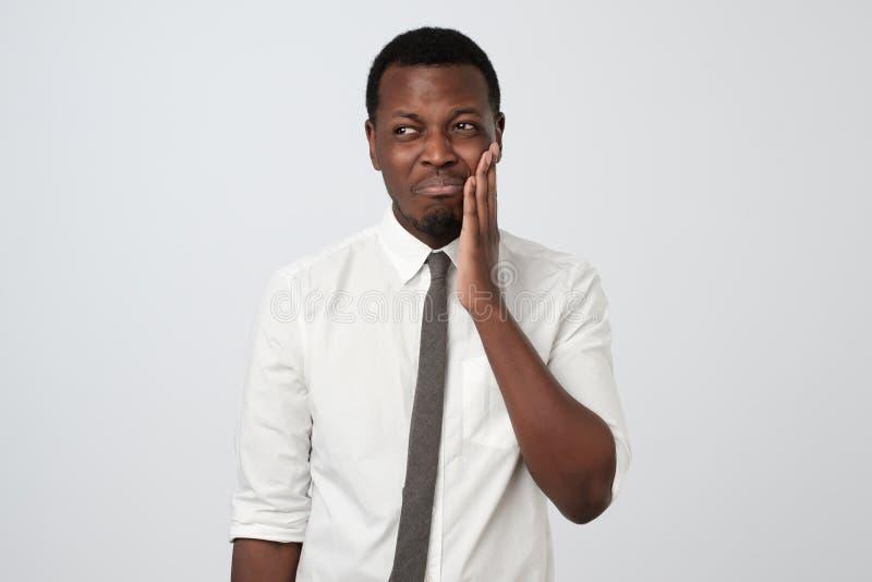 Jeune homme africain frustrant touchant sa douleur de joue de douleur photos libres de droits