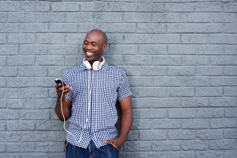 Jeune homme africain heureux avec les écouteurs et le téléphone portable photo libre de droits