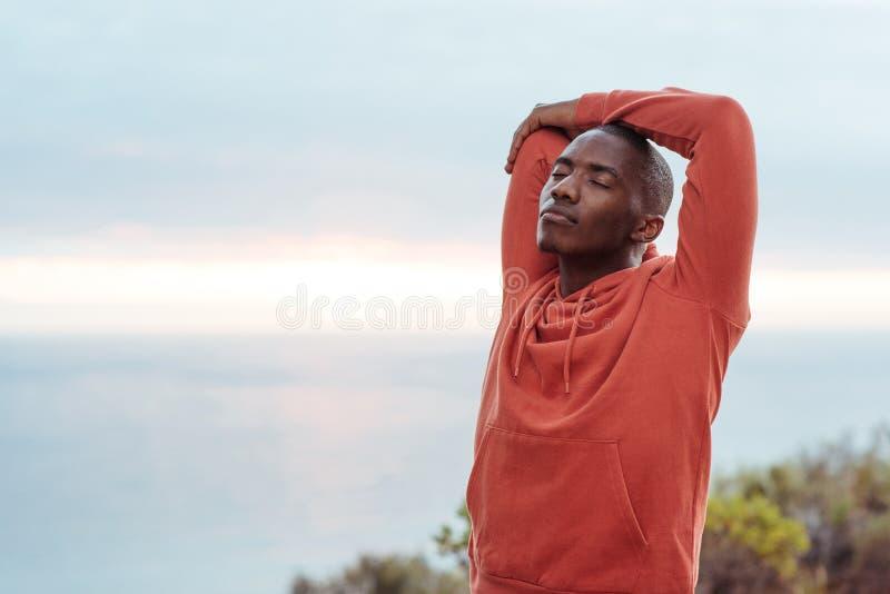 Jeune homme africain s'étirant avant une course le long de l'océan photographie stock