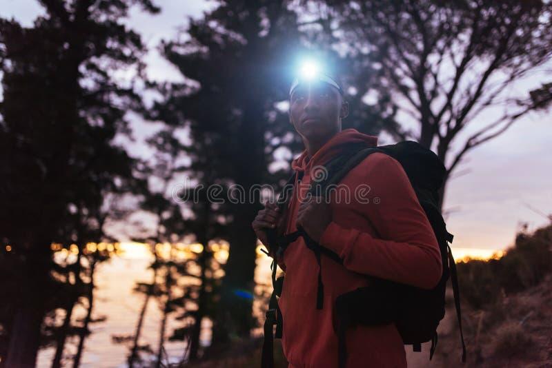 Jeune homme africain seul trimardant dans les bois au crépuscule photo libre de droits