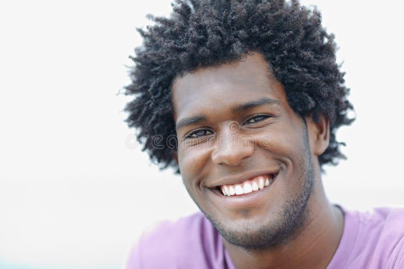 Jeune homme africain souriant à l'appareil-photo photo stock