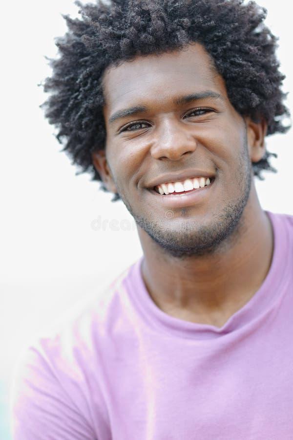 Jeune homme africain souriant à l'appareil-photo photos stock