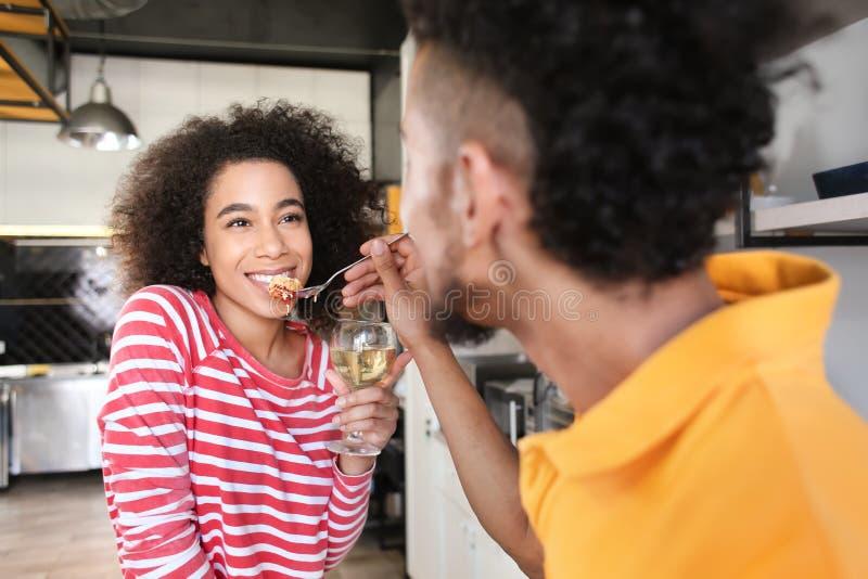 Jeune homme afro-américain alimentant son amie dans la cuisine image libre de droits