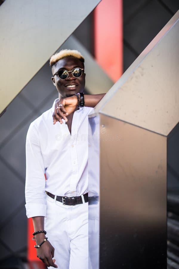 Jeune homme afro-américain beau portant les vêtements élégants à l'arrière-plan moderne de ville image stock