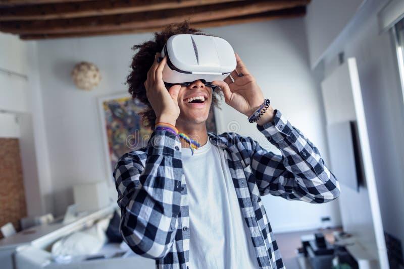 Jeune homme afro-américain heureux employant ses verres de réalité virtuelle tout en se tenant à la maison photo libre de droits