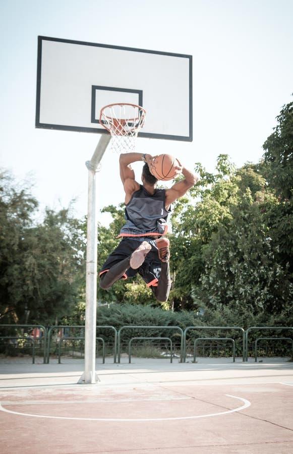 Jeune homme afro-américain jouant le basket-ball de rue en parc images libres de droits
