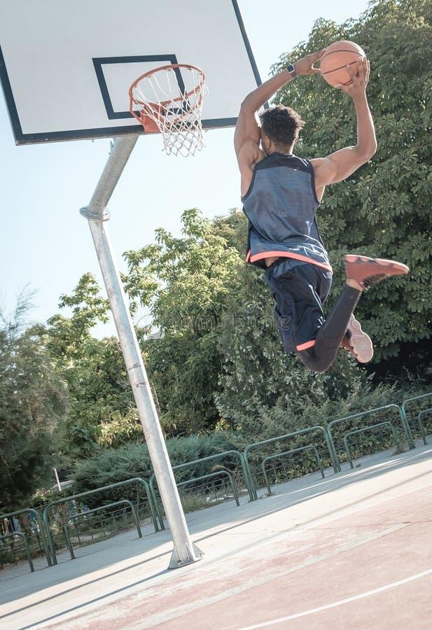 Jeune homme afro-américain jouant le basket-ball de rue en parc photos stock