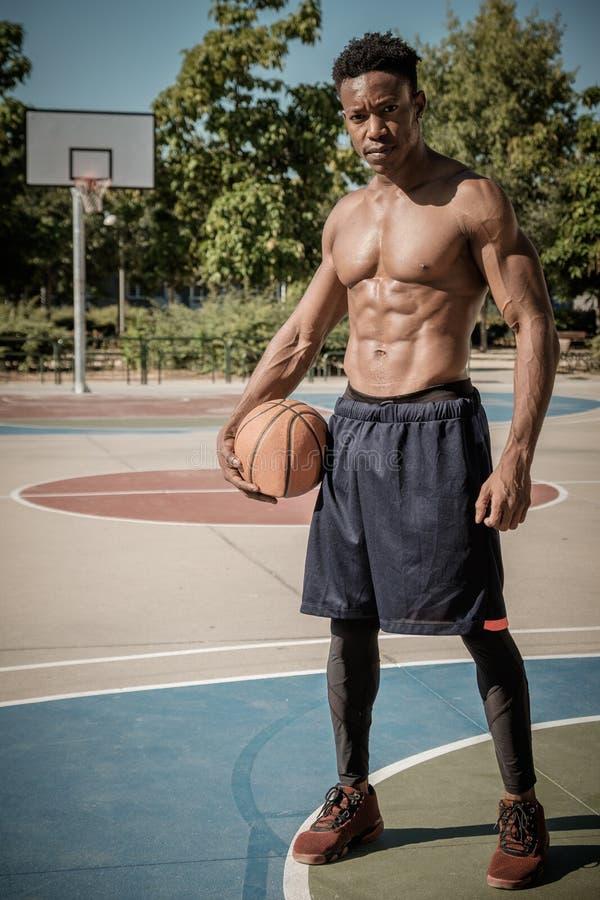 Jeune homme afro-américain jouant le basket-ball de rue en parc photos libres de droits