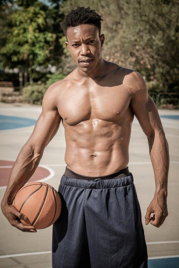 Jeune homme afro-américain jouant le basket-ball de rue en parc image stock