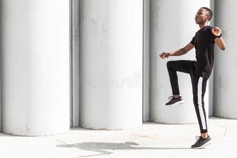 Jeune homme afro-américain sportif courant sur la promenade Coureur masculin noir sprintant dehors Style de vie sain image stock
