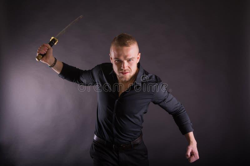 Jeune homme agressif tenant l'épée de katana regardant l'appareil-photo Sur le fond de mur photo stock