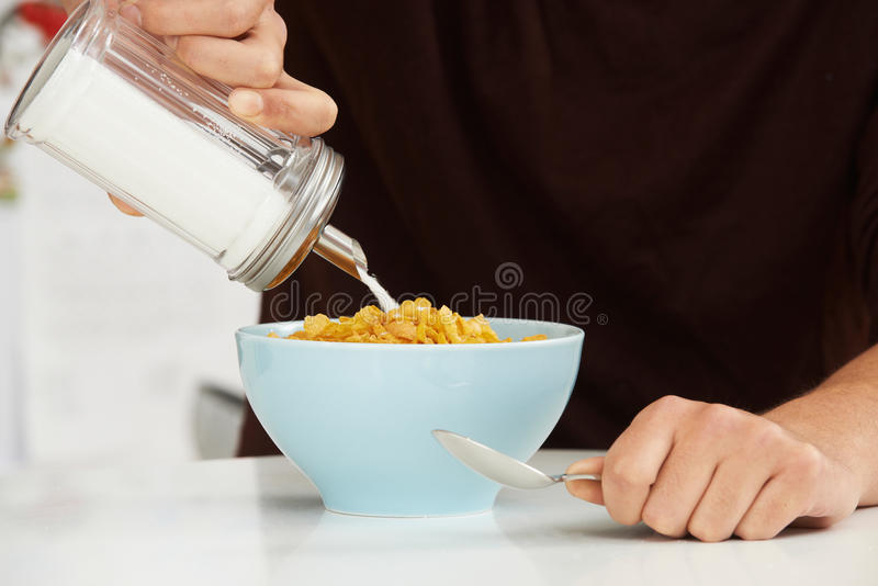 Jeune homme ajoutant Sugar To Breakfast Cereal image stock