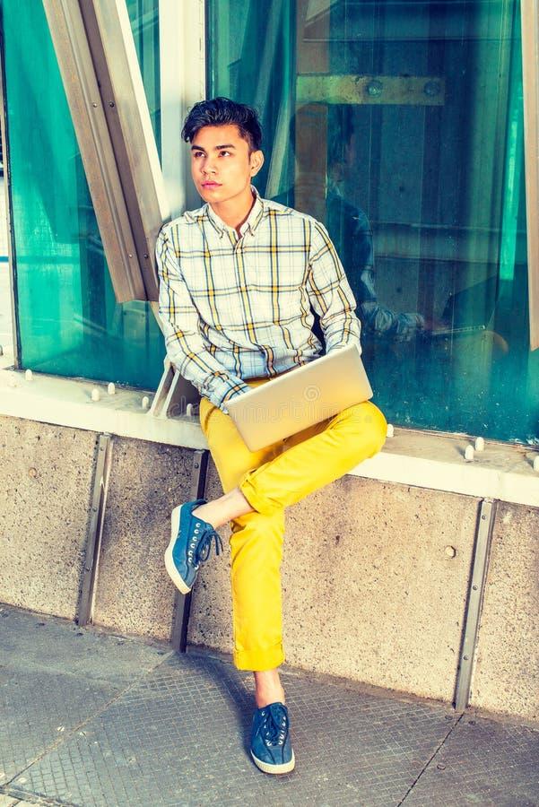 Jeune homme américain asiatique travaillant sur l'ordinateur portable dehors dans N photo libre de droits