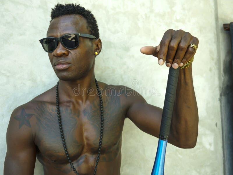 Jeune homme américain d'africain noir attirant et bel avec le corps musculaire convenable et six des poses de batte de baseball  photographie stock libre de droits