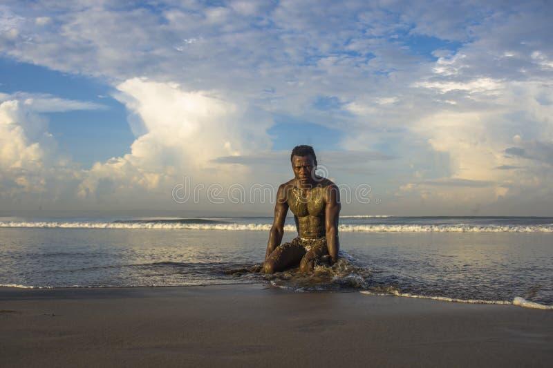 Jeune homme américain d'africain noir attirant et sexy avec le corps musculaire sexy se mettant à genoux sur bel apprécier tropic photo stock