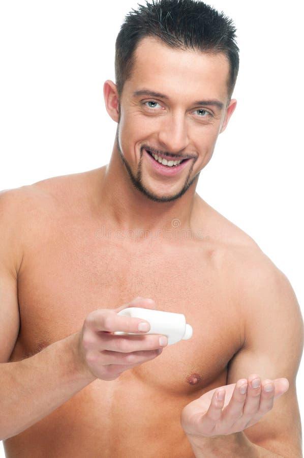 Jeune homme appliquant la crème. Produit de beauté photo stock